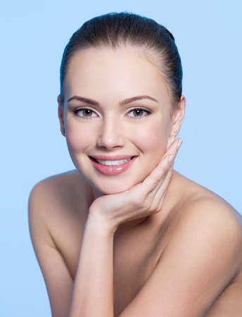 vertical: Cara feliz hermosa ni�a adolescente con una piel sana limpia - fondo azul