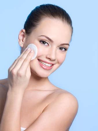 dentudo: Chica adolescente feliz cuidada sobre su piel sana fresco de cara con fondo de disco - azul con un hisopo de algod�n