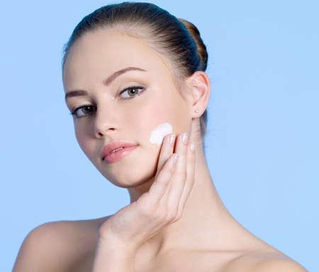 Beautiful teen girl applying moisturizing cream on her cheek - blue background photo
