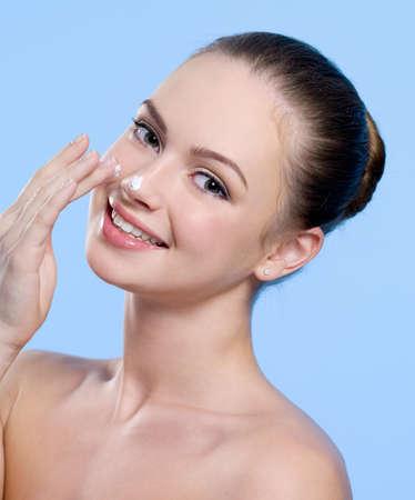nariz: Retrato de joven hermosa sonriente con crema de su fondo de nariz - azul Foto de archivo