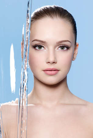 Beautiful young face of woman with clean skin on it and stream of water - blue background photo