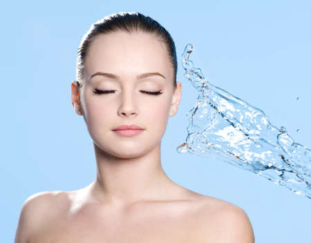 Clean skin on the face of young beautiful young woman and stream of water - blue background photo