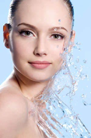 caucasian water drops: Portrait of young female face with splash of water - blue background