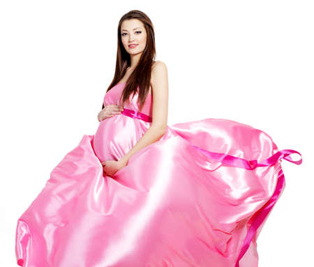 Glamour ans stylish  pregnant beautiful woman in pink blowing dress - white background photo