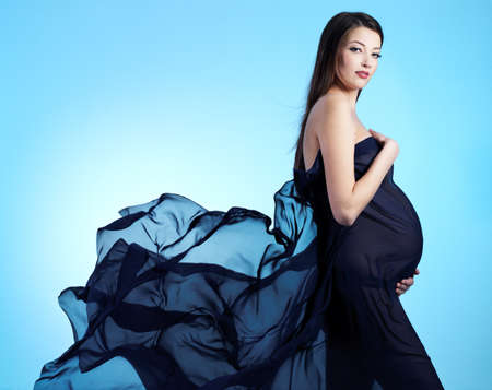 Young beautiful sexy and stylish  pregnant woman in blue - blue background photo