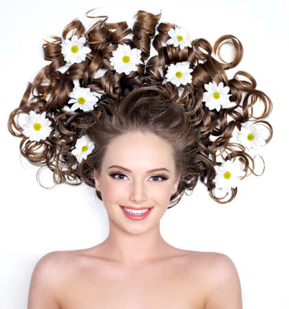Smiling young woman with flowers in her gorgeous long hair - white background photo