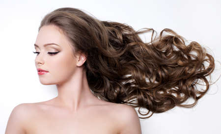 Young woman with beautiful long curly hair - white background photo