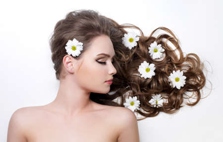 Flowers in beautiful gorgeous long curly hair of young woman - white background Stock Photo - 9115421