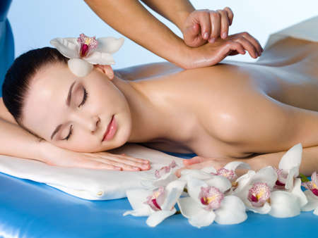 salon spa: Relaxing massage of back for young beautiful woman in spa salon - horizontal