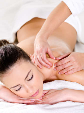 body spa: Young beautiful woman having massage on her shoulder - vertical Stock Photo