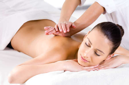massage spa: Relaxing massage for young beautiful woman in the spa salon - horizontal