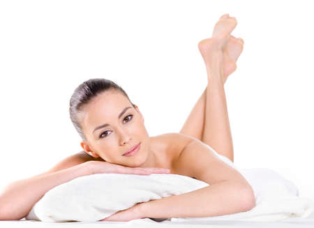human bodies: Relaxing young beautiful woman with fresh skin - white background. Lying on bed Stock Photo