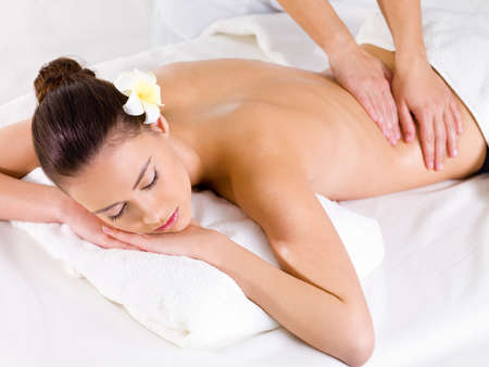 Massage for the back of young beautiful woman in spa salon - indoors photo