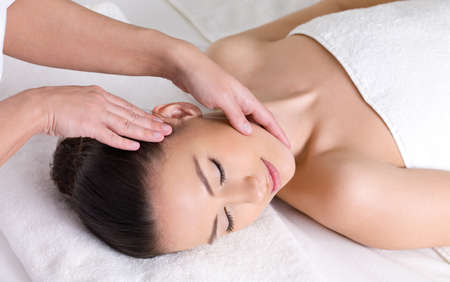 face massage: Young woman having massage for the skin of her beautiful face Stock Photo