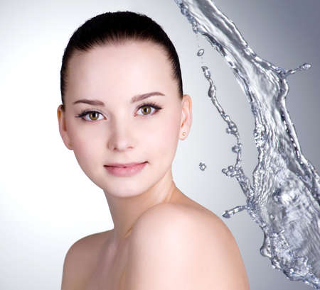 Beautiful face with clean skin and splashes of water - colored background photo