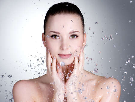 Portrait of beautiful young woman with drops of water around her face - horizontal photo