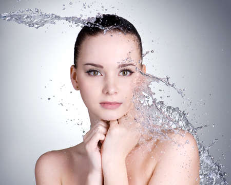 Beautiful healthy woman with clean fresh skin and splashes of water  - grey background photo