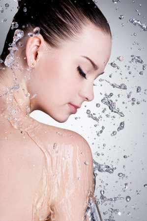 Splashes and drops of water around the female face with clean skin - vertical photo