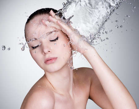 Water falling on the beautiful sensuality woman face with clean skin - horizontal Stock Photo - 9195348