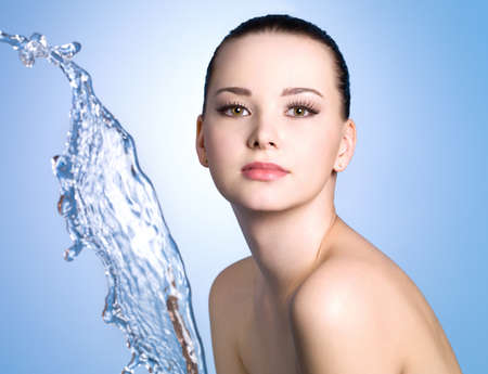 Beautiful girl with clean skin and stream of water near her face - blue background photo