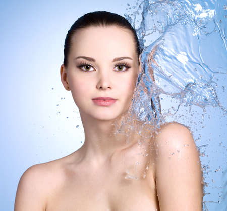 Beautiful young woman with splashes of water on her body- colored background photo