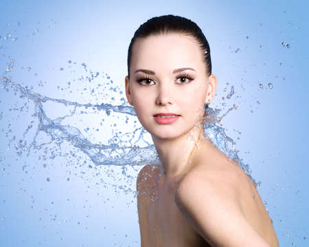 Beauty splashes of water for the young beautiful woman with clean skin - blue background photo