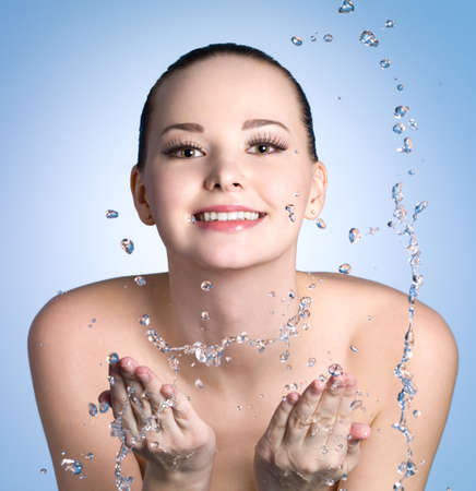 bodycare: Happy young woman washing her face with clean water