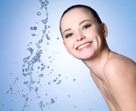 Portrait of happy cheerful young girl with splashes of water - blue background Stock Photo - 9244615