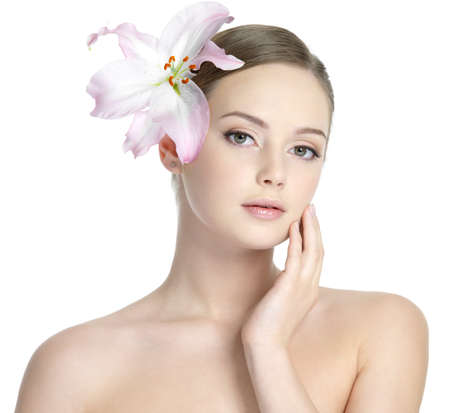 beautiful sensuailty  woman with lily on the head stroking her face with healthy clean skin - isolated on white photo