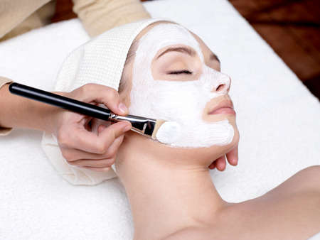 masajes faciales: Cosmet�loga aplicar m�scara de belleza facial para la joven y bella mujer en sal�n de spa