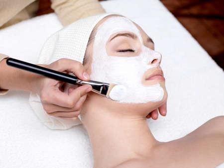 facial massage: Il appliquer le masque de beaut� du visage pour la jeune femme belle au salon de spa Banque d'images