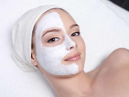 facial mask: Beautiful young woman getting facial mask at beauty salon - indoors Stock Photo
