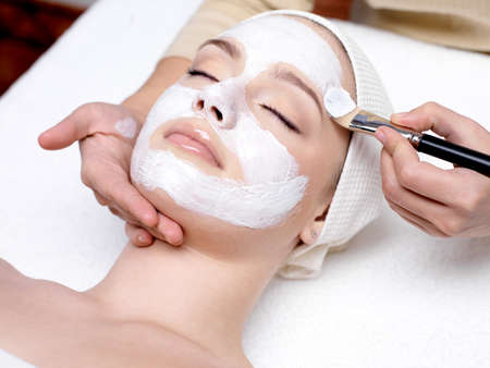 Beautiful young woman receiving facial mask at beauty salon - indoors Stock Photo