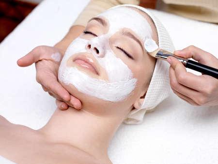 facial massage: Belle jeune femme re�oit un masque facial au salon de beaut� - � l'int�rieur