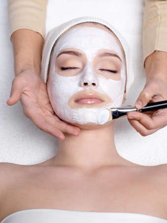 Cosmetician apllying facial mask to the face of young beautiful woman in spa salon - vertical photo