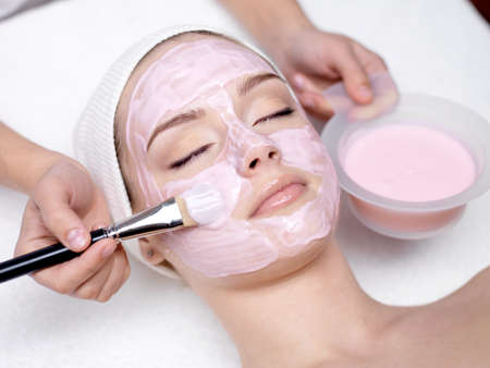 salon: Young beautiful girl receiving pink facial mask in spa beauty salon - indoors