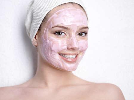 femme masqu�e: Portrait de femme souriante de bel jeune avec masque de beaut� du visage rose Banque d'images