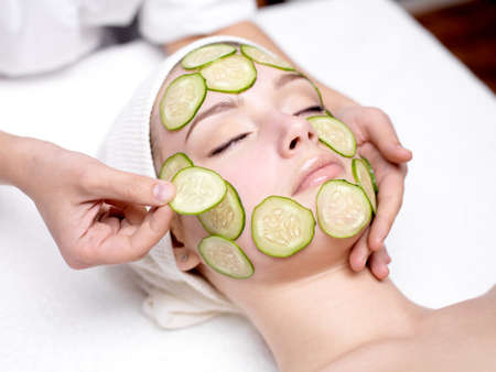 cucumber: Beautiful young woman receibing facial mask of cucumber in beauty salon - indoors