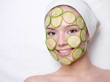 Happy smiling young woman with facial mask of cucumber - white background Stock Photo - 9244704