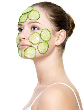 skincare facial: Portrait of young beautiful adult girl with facial mask of cucumber - isolated on white