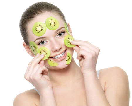 Happy young beautiful woman with a fruit kiwi mask on a face - isolated on white background photo
