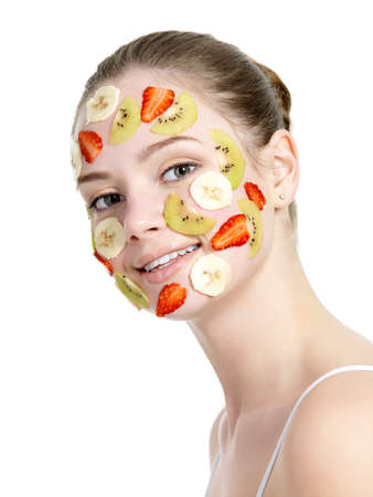 vertical wellness: Smiling beautiful young woman with fruit mask on her face - white background