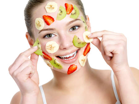 Portrait of happy cheerful young beautiful woman with fruit facial mask - isolated on white photo