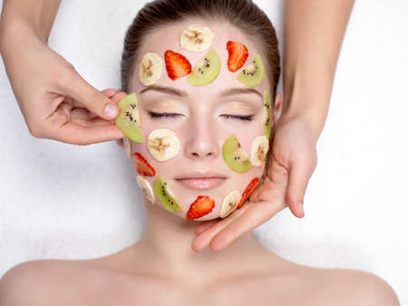 Cosmetician doing fruit mask on a face of beautiful young woman - indoors photo