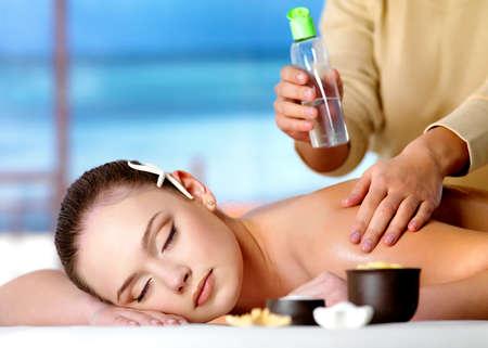 Giovane donna bella rilassante, ottenendo il massaggio con olio cosmetico in spa salon - sfondo di natura