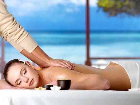 woman massage: Relaxing woman in a resort having spa healthy massage - horizontal Stock Photo