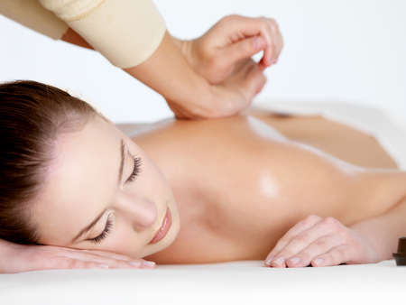 massage: Relaxing massage on a back for young beautiful woman - white background Banque d'images