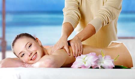 Sonriente chica recibiendo masaje spa en salón de belleza - fondo de naturaleza. En el interior Foto de archivo - 9267819