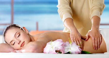 Young woman  relaxing in spa salon and getting massage of body - nature background photo