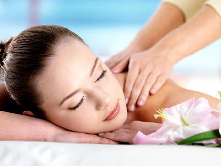 face massage: Beautiful young girl with attractive face having a massage for  shoulder on resort - colored background Stock Photo